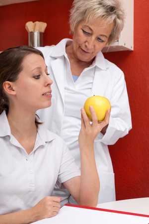 patient's history: nurse staff making a break, one with an apple, the older one standing behind her