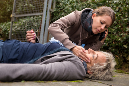 1st: senior adult had an collapse, a young woman do first aid Stock Photo