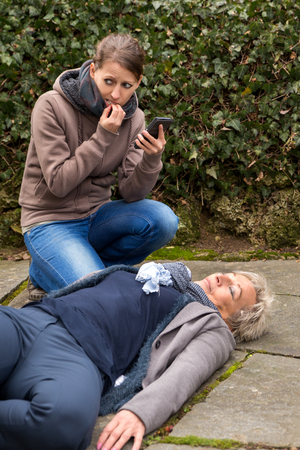 reanimate: young woman do an emergency call, cause a senior adult is lying on the ground