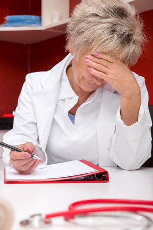 doctor burnout: aged femlae doctor is stressed, documents on a table