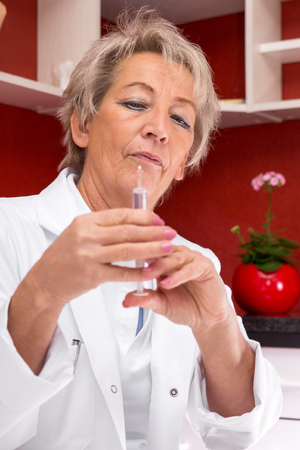 nurse injection: portrait of an aged female doctor with syringe in her hand Stock Photo