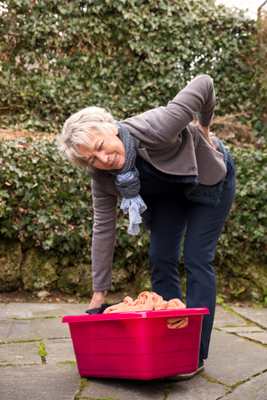 seniors suffering painful illness: woman with back pain, trying to carry weight