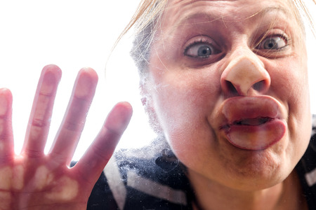 against: woman with fish mouth at the window makes a funny grimace