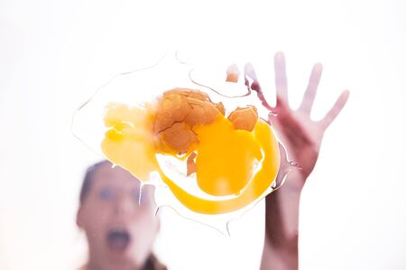 smashed: surprised woman with smashed egg, below studio shot