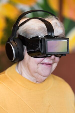 funny senior adult with virtual reality glasses is having fun, watching a movie photo
