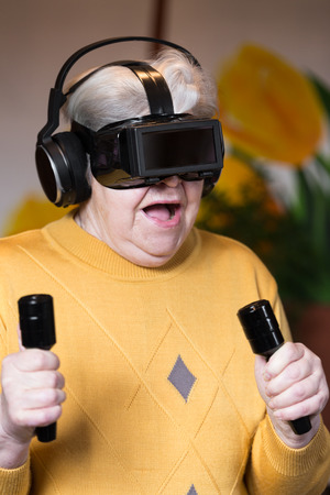 elderly woman with gaming simulator and controller is looking surprised photo