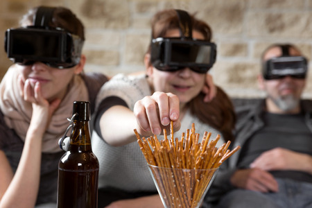 virtual reality simulator: three people with virtual reality glasses and snacks, having fun Stock Photo