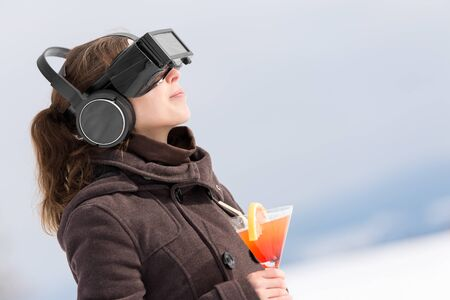fissure: woman in snow is wearing virtual reality glasses and dreams of summer holiday with a cocktail in her hand