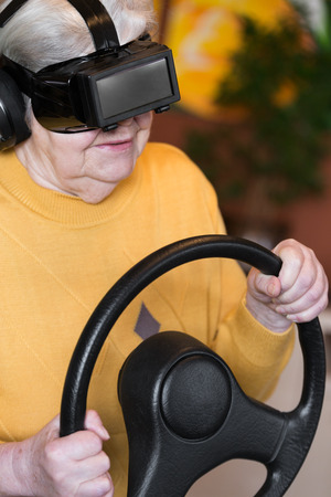 senior adult with virtual reality glasses and steering wheel photo