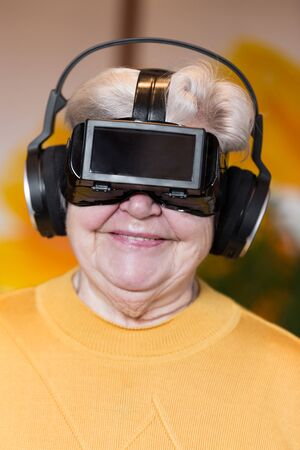 funny senior adult with virtual reality glasses is having fun photo