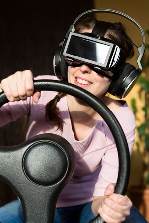 virtual reality simulator: woman with a driving simulator and virtual reality glasses
