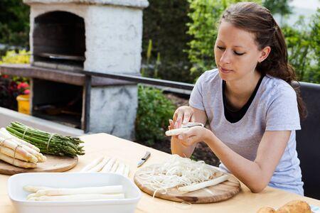 mujeres trabajando: la mujer está pelando espárragos verdes y blancos Foto de archivo