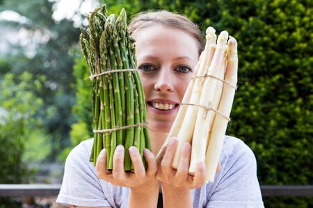 funny woman is holding sundry asparagus in front of her face, horicontal