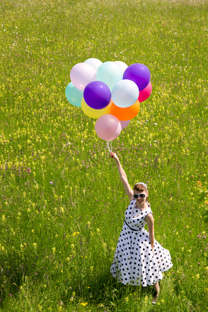 petticoat: Pinup Girl with a white dotted petticoat dress and colorful balloons on the meadow, topview