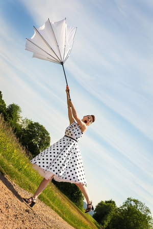 petticoat: pretty Pin up Girl with a petticoat and a umbrella is blowing off the path