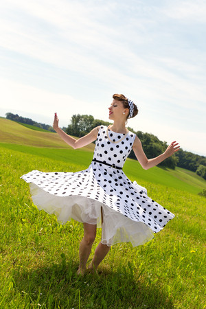 petticoat: Pin up or rockabilly Girl with rock n roll outfit is dancing and twisting on the meadow