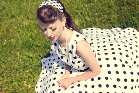 petticoat: woman with a petticoat dress, a braid and a suicide roll sitting on the meadow, concept style and fashion