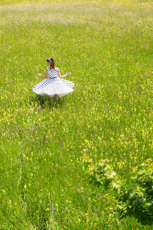 hair band: Pin up Girl with a petticoat dress and hair band is twisting in a wildflower meadow Stock Photo