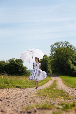 hairband: woman in a vintage fifties outfit with petticoat, hairband and a parasol is walking on a path in the nature