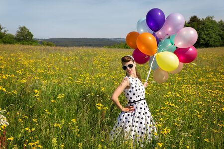 pinup girl: beautiful pinup girl with colorful balloon on a meadow