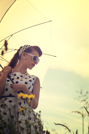 petticoat: young pretty woman with a vintage rockabilly outfit and a sunshade in a meadow, backlight Stock Photo
