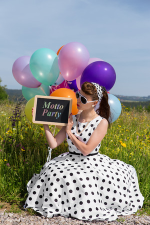 petticoat: Retro Girl with a petticoat dress and sunglasses holding a board with text Motto Party, concept invitation and theme party