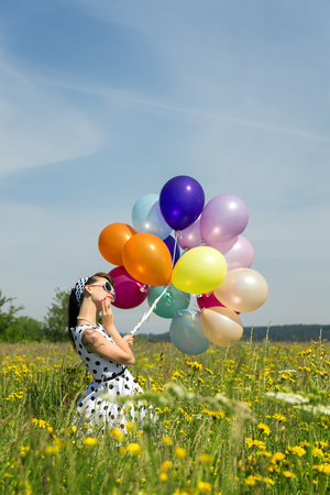 fifties: beautiful woman in a fifties dotted dress and a lot of colorful balloons on a flowery meadow