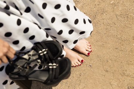 woman barefoot: barefoot woman with a petticoat dress holding her shoes, concept lifestyle