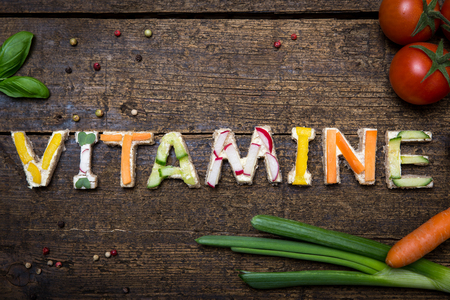 vitamine: letters of fresh vegetable canapes builds the german word vitamine on a old wooden table