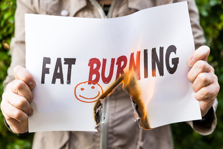 Woman is holding burning paper, with the sentence fat burning