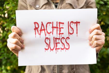 frase: La mujer está sosteniendo un papel con la frase alemán Rache ist Suess, significa dulce venganza