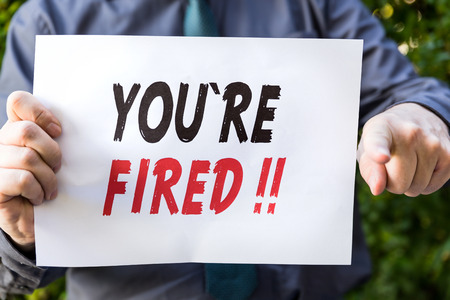 you are fired: Businessman is holding a  paper with  text, you are fired