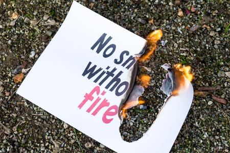 oracion: la quema de papel en el suelo, con la frase no hay humo sin fuego Foto de archivo