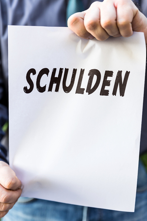 savings problems: businessman is holding a paper with german word schulden, means debts