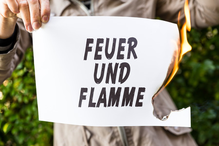 Woman is holding a burning paper with german text feuer und flamme, means to be on fire Stock Photo