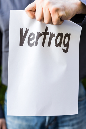 broken contract: Businessman is holding a paper with german word vertrag, means contract