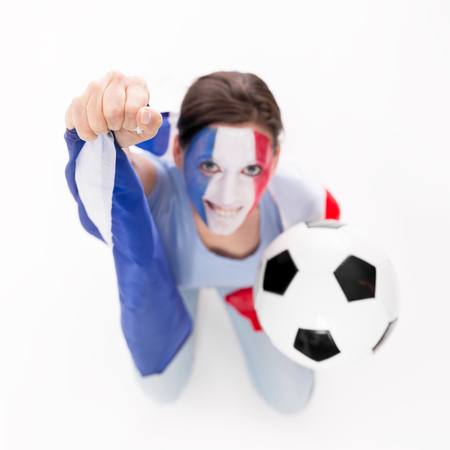 soccer team: female soccer fan from the national Team of France is cheering, flag and football in the hands