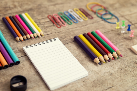 paperclips: Office desktop with colorful pencils, notepad, supplies and paperclips, wooden table