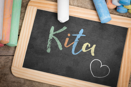 kita: Slate with german word Kita, which means Kindergarten, colorful crayon on wooden Table, flat lay