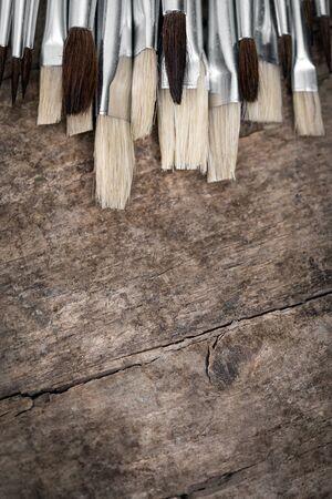 unused: lot of unused brushes on a wooden background, vintage filtered