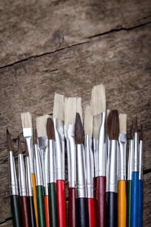 unused: lot of unused brushes on a wooden background, vintage filtered, topview