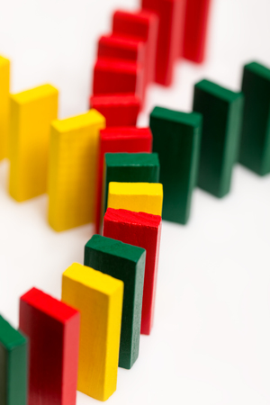 coming together: colorful dominos on white background coming together, concept connection or global networking, vertical Stock Photo