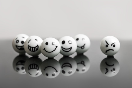 misfit: white marbles with faces on a black stone with reflections. concept teamwork and success with one misfit