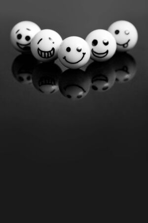 teamwork concept: white marbles with faces on a black stone with reflections. concept teamwork and success