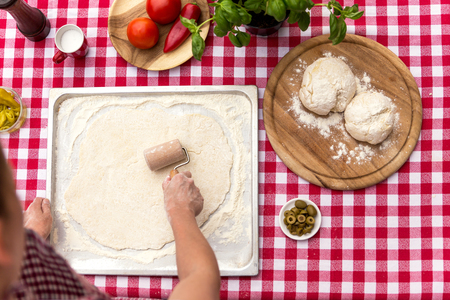 cook griddle: woman is rolling out dough, vegetables and herbs, red white tablecloth, dough balls on a wooden board