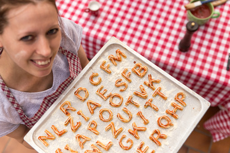 griddle: woman is holding a griddle, pizza dough with tomatoe sauce, letters Stock Photo