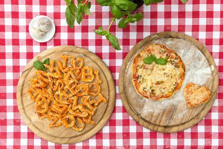 cook griddle: baked pizza letters on a wooden board, red white tablecloth, fresh basil, pizza heart Stock Photo