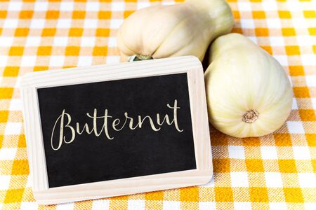 butternut squash: Butternut squash on a chequers tablecloth and a slate with Word Butternut