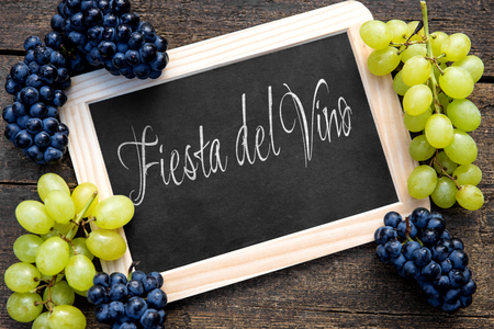 vino: white and blue grapes with a slate on wooden table, spanish text fiesta del vino on it, which means wine festival