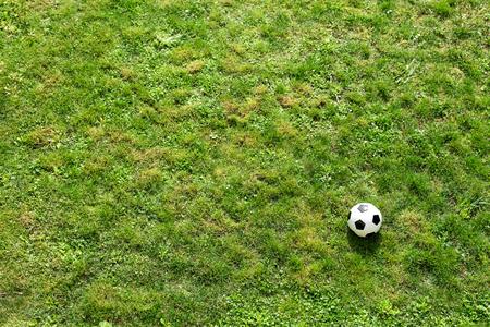 match: Soccer ball on green turf, flat lay, copyspace